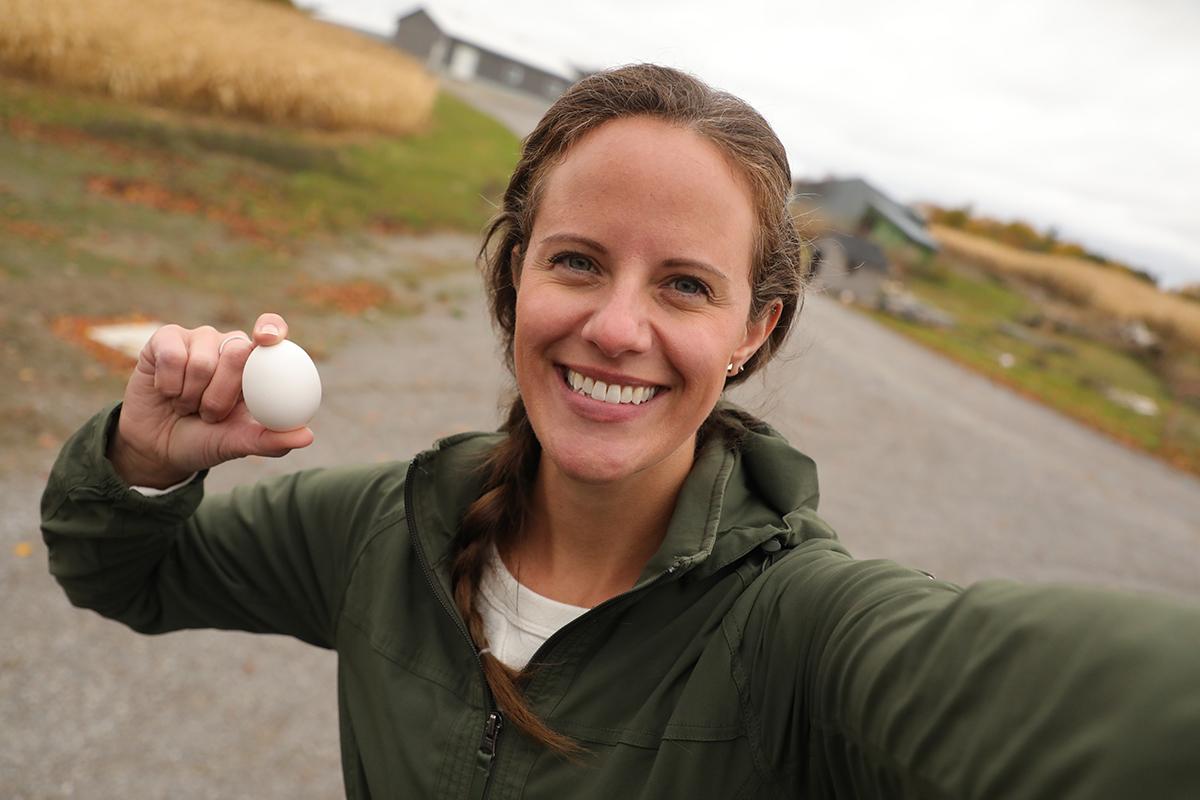 woman farmer holder an egg outdoors