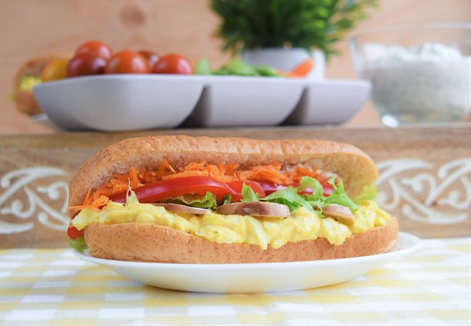 Egg Salad Sub Sandwich with veggies in the background