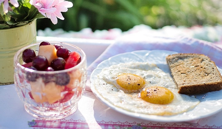 Fried eggs plated next to flowers on an outdoor table